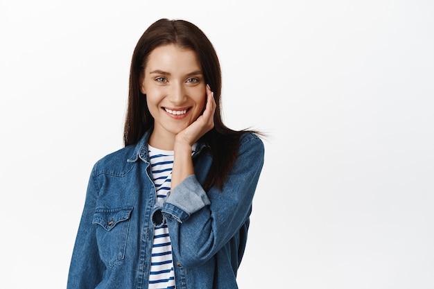 Femme souriante satisfaite de l'état de la peau du visage, concept de traitement de la clinique de cosmétique et de beauté, touchant un visage propre et brillant sur blanc.