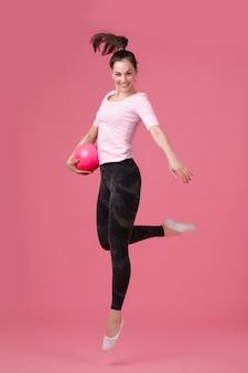 Femme souriante sautant avec le ballon