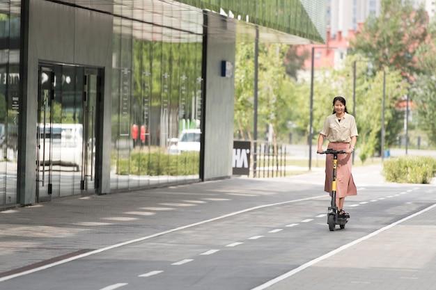 Femme souriante avec scooter plein coup