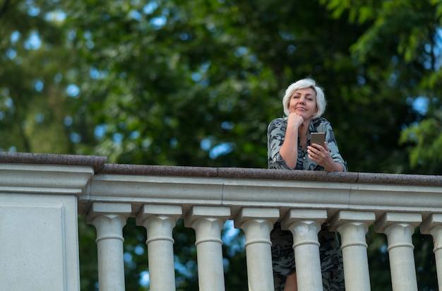 Femme souriante se penchant sur un parapet en regardant la caméra sur un fond d'arbres verts feuillus