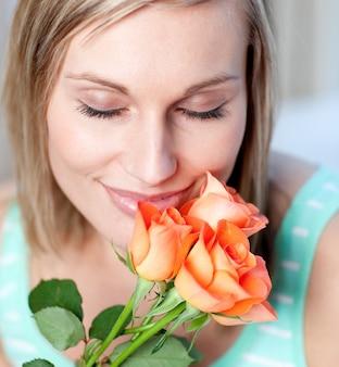 Femme souriante, sentant les roses
