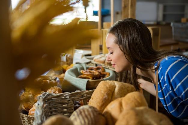 Femme souriante, sentir une collation de boulangerie au comptoir
