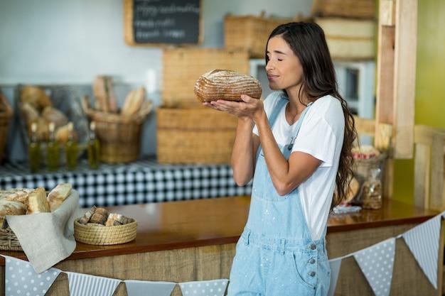 Femme souriante, sentir une miche de pain ronde au comptoir