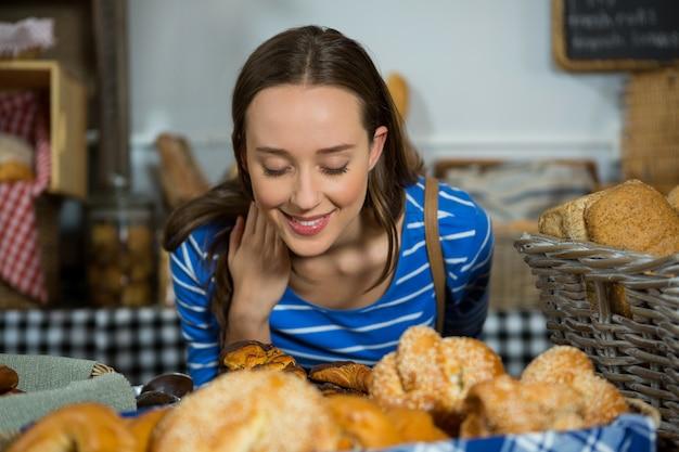 Femme souriante, sentir un pain au comptoir