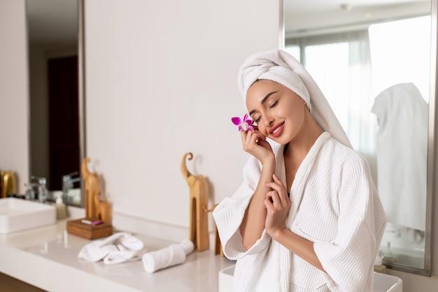 Une femme souriante avec une serviette sur la tête et dans une robe de chambre