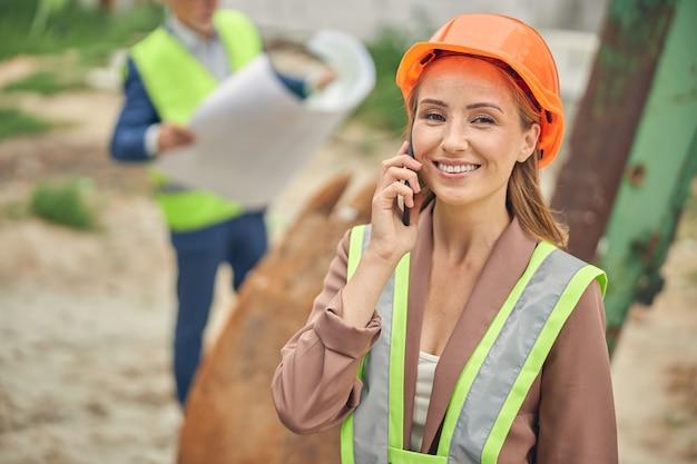 Femme souriante avec un smartphone et un ingénieur civil avec un dessin technique travaillant à l'extérieur