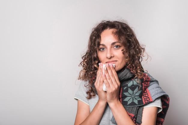 Femme souriante souffrant de rhume et de grippe sur fond gris
