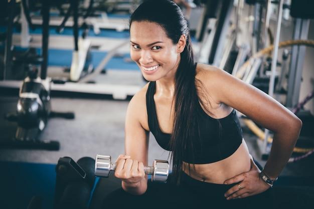 Femme souriante soulever des poids