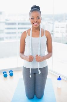 Femme souriante en sportswear tenant un ruban à mesurer autour du cou