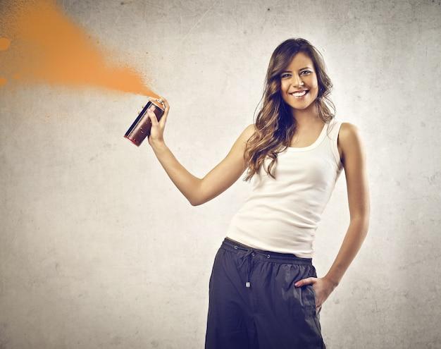 Femme souriante avec un spray de peinture