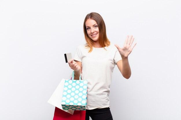 Femme souriante et sympathique, montrant le numéro cinq ou cinquième avec la main vers l'avant, compte à rebours