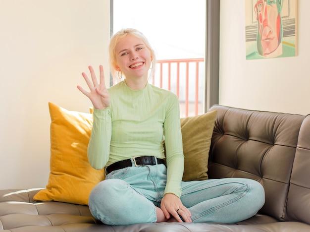 Femme souriante et à la sympathique, montrant le numéro quatre ou quatrième avec la main en avant, compte à rebours