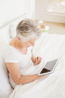 Femme souriante avec tablette assise sur le lit