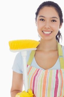 Femme souriante en tablier avec balai