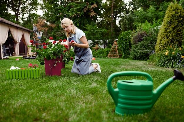 Femme souriante en tablier travaille avec des fleurs dans le jardin