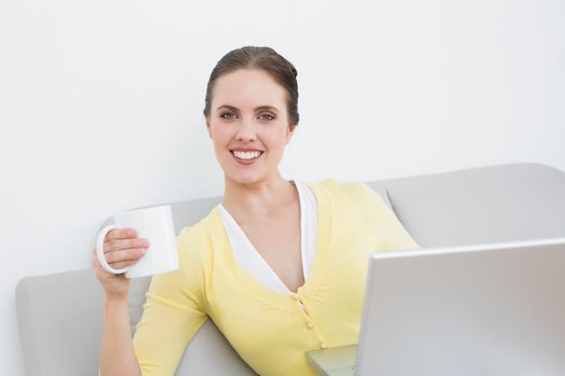 Femme souriante avec une tasse de café et un ordinateur portable assis à la maison