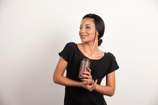 Femme souriante avec une tasse de café posant sur un mur blanc.