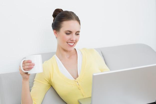 Femme souriante avec une tasse de café en utilisant un ordinateur portable à la maison