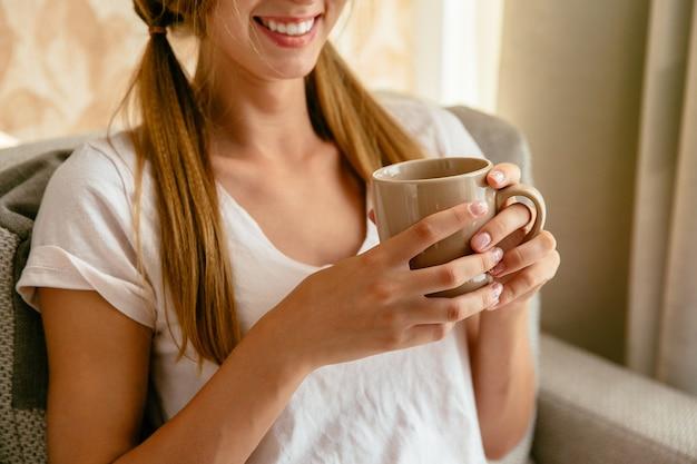 Femme souriante avec une tasse de thé dans les mains à la maison. fermer