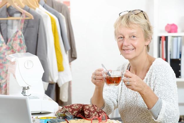 Une femme souriante avec une tasse de thé dans son atelier de couture