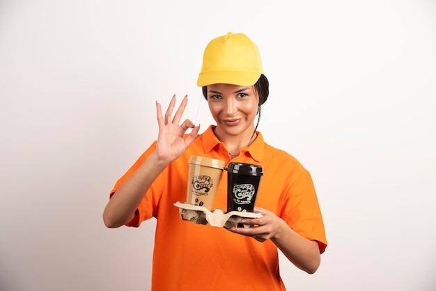 Femme souriante avec des tasses montrant un geste ok