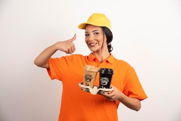 Femme souriante avec des tasses montrant le pouce vers le haut