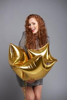 Femme souriante tenant des ballons en forme d'étoile au studio shot
