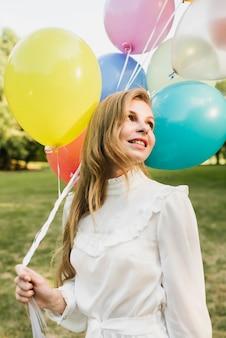 Femme souriante tenant des ballons en plein air