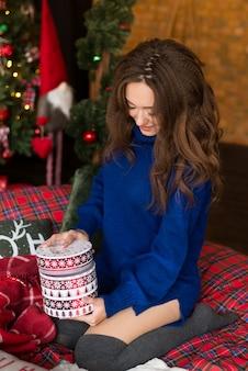 Femme souriante tenant une boîte cadeau