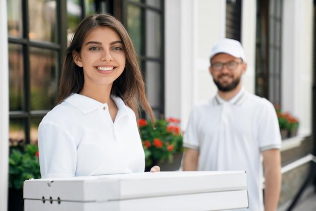 Femme souriante tenant des boîtes de pizza