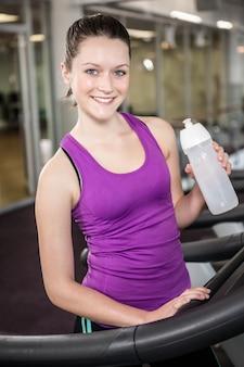 Femme souriante tenant une bouteille d'eau dans la salle de sport