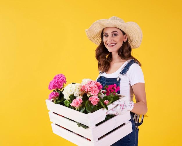 Femme souriante tenant une caisse en bois avec des fleurs