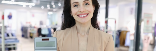 Femme souriante tenant une calculatrice et une tirelire sur fond de centre commercial
