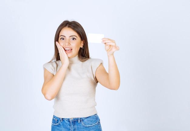 Femme souriante tenant une carte sur fond blanc.
