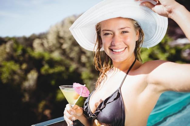 Femme souriante tenant un cocktail et regardant la caméra