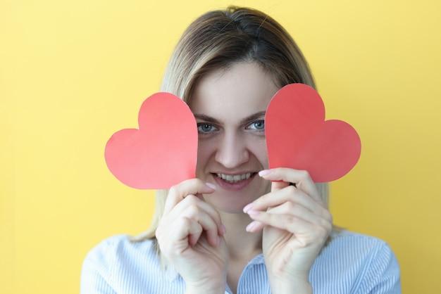 Femme souriante tenant des coeurs rouges dans ses mains