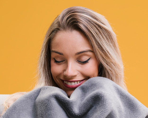 Femme souriante tenant une couverture avec les yeux fermés à la maison