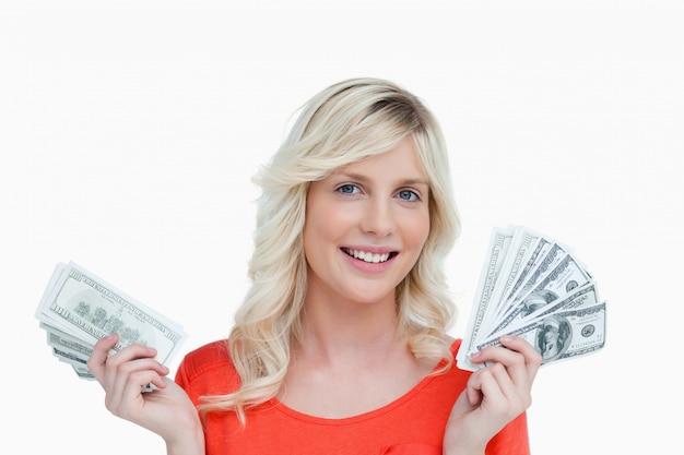 Femme souriante tenant deux fans de billets de dollar dans ses mains