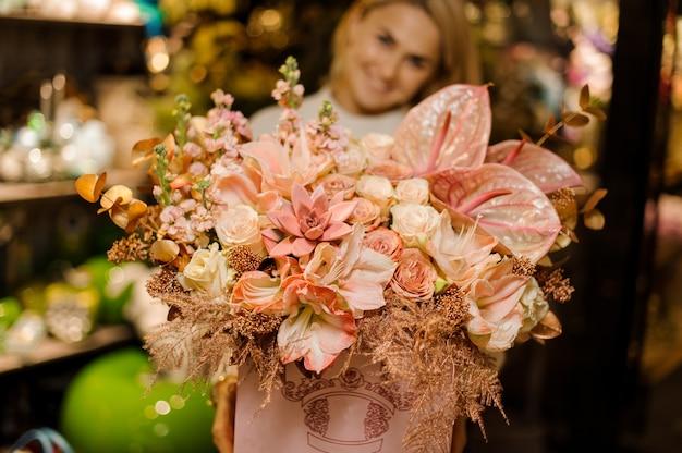 Femme souriante tenant une énorme boîte de roses de couleur rose vif, succulettes et callas avec décor doré