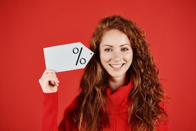Femme souriante tenant une étiquette de prix vierge
