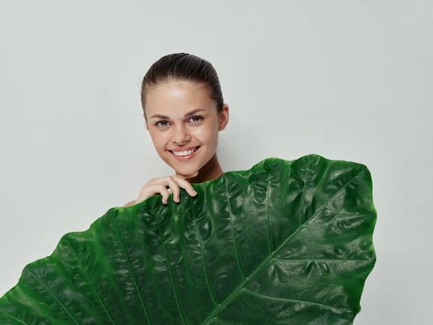 Femme souriante tenant une feuille verte devant son fond clair exotique