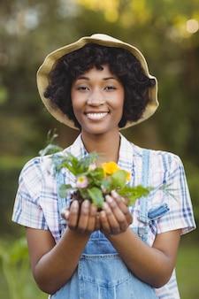 Femme souriante tenant des fleurs dans le jardin