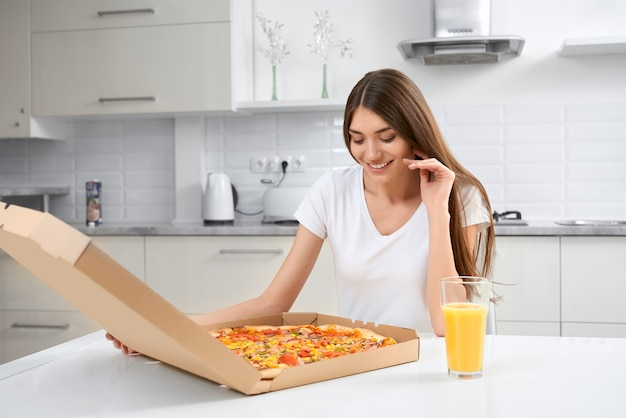 Femme souriante tenant une grosse pizza savoureuse