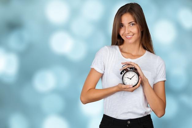 Femme souriante tenant une montre d'alarme