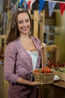 Femme souriante tenant un panier de tomates dans l'épicerie