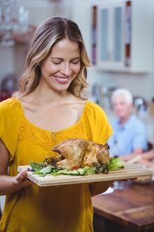 Femme souriante tenant une planche à découper avec de la viande