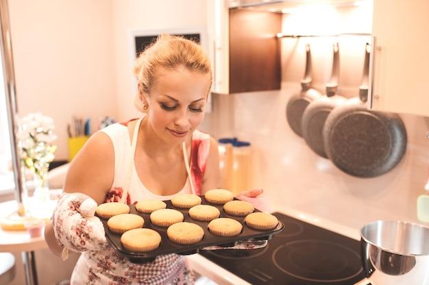 Femme souriante tenant une plaque de cuisson avec des muffins