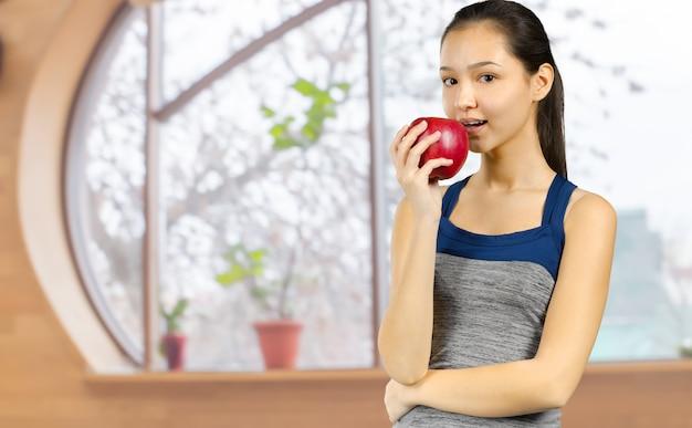 Femme souriante tenant une pomme rouge