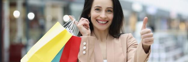 Femme souriante tenant les pouces vers le haut et les sacs à provisions