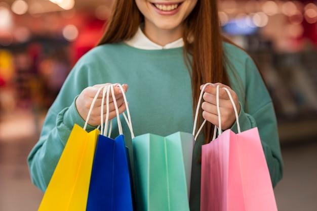 Femme souriante tenant des sacs en papier colorés